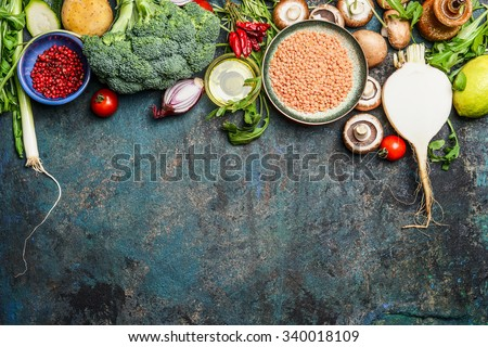 variety of vegetables, red lentil and ingredients for healthy cooking on rustic background, top view, horizontal border. Vegan food or diet eating concept. - stock photo