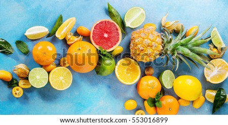 Variety of whole and sliced citrus fruits pineapple, grapefruit, lemon, lime, kumquat, clementine, physalis with mint over blue wooden background. Top view with space. Healthy eating, dieting. Banner