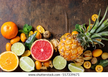 Variety of whole and sliced citrus fruits pineapple, grapefruit, lemon, lime, kumquat, clementine and physalis with mint over dark wooden background. Top view with space. Healthy eating, dieting