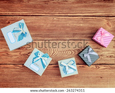 Variety of Wrapped Gift Boxes Arranged According to Size in Curved Line on Wooden Background as seen from Above - stock photo