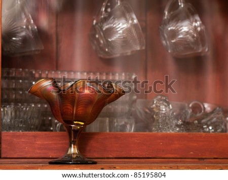 Various antique glassware pieces displayed in an antique hutch.
