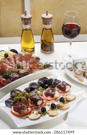 Various appetizer, glass of red wine and seasoning oil arranged and served at the table. - stock photo
