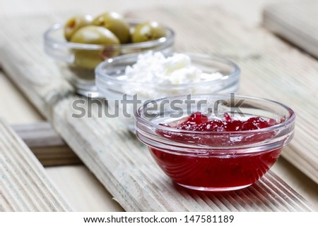 Various appetizers: olives, cranberry, cottage cheese in small bowls on wooden background. Selective focus