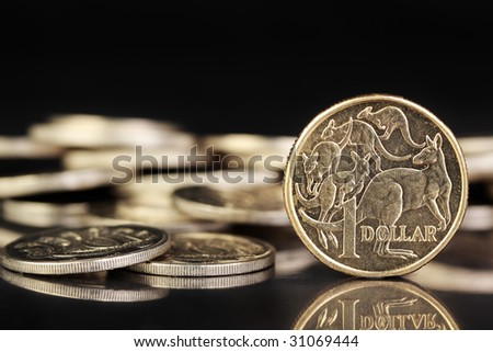 Various australian coins on a dark reflective surface. - stock photo