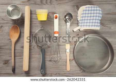 Various baking tools arrange from overhead view on wooden table in vintage tone. - stock photo