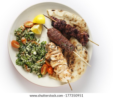 Various barbecued kebabs - kofta, chicken tawook and sumac chicken - with tabouleh and pitta bread; an Arab or Lebanese-style feast, seen from above