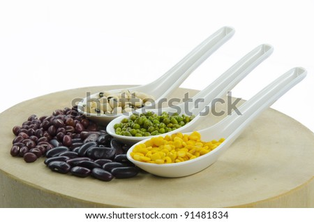 Various beans on spoon stacked on wood plate.