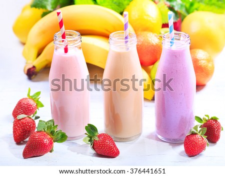 various bottles of smoothie with fresh fruits - stock photo