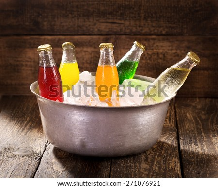 various bottles of soda in the bucket with ice on wooden table - stock photo