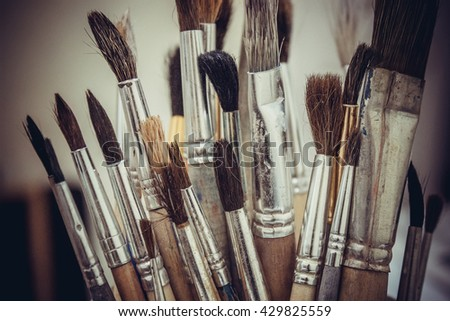 Various brush to paint on a pale green background. - stock photo