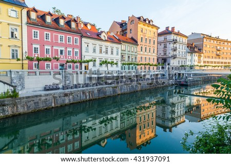 Various buildings in Ljubljana along the river. Reflections can be seen in the water - stock photo