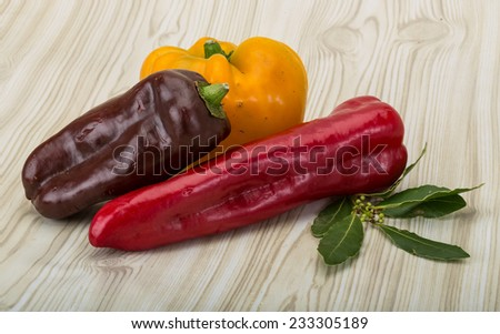 Various Bulgarian peppers with laurel leaves on the wood background - stock photo