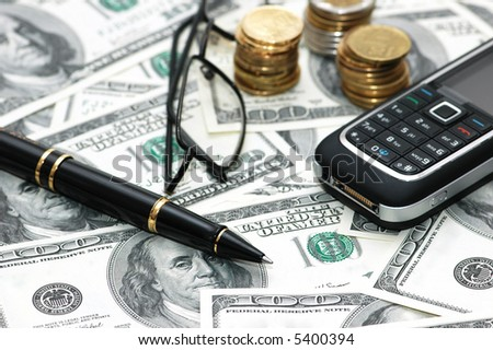 Various business objects over hundred dollar bills