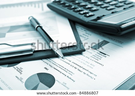 Various business stuff on a desk - blue toned image