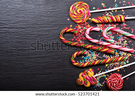 various candy canes on dark background, top view with copy space.