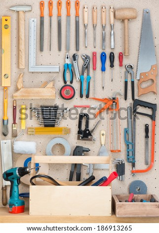 Various carpentry, construction tools hanging on the board. - stock photo