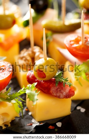 Various cheese skewers  on a black background. Delicious appetizers with cheese and mix ingredients - stock photo