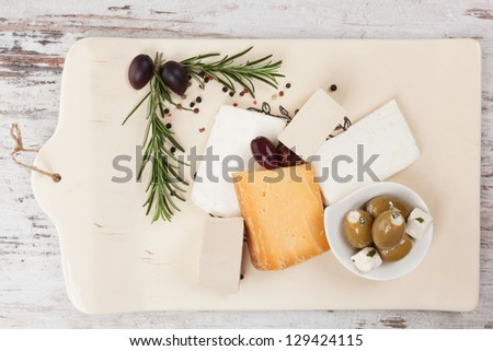 Various cheese, tofu and olives on vintage kitchen board on white wooden textured background top view. Culinary cheese and olives eating, french country style starter. - stock photo