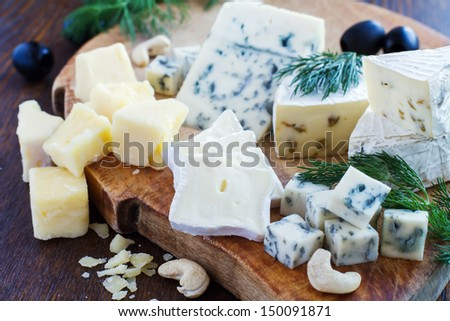 various cheeses on a wooden background - stock photo