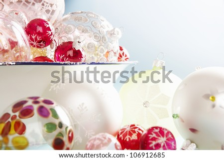 Various Christmas balls pouring out of a glitter container against a blue background. - stock photo