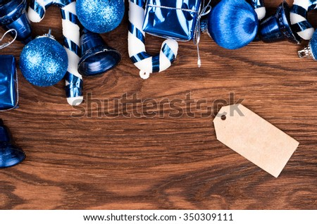 Various Christmas toys on the tree and the label for the discounts and prices on the wooden background - stock photo