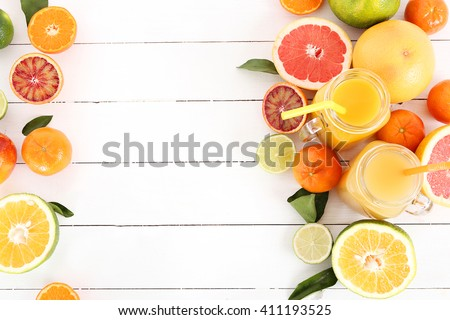 Various citrus fruits with a drink on the table - stock photo