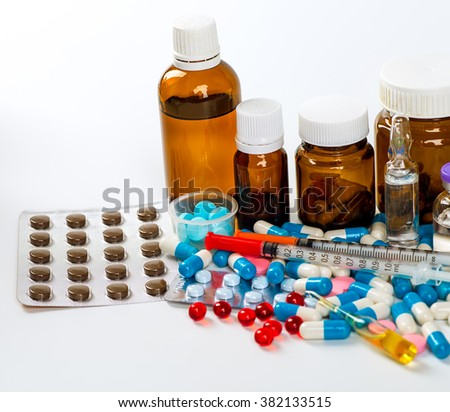 Various cold prescription bottles and a syringe isolated on a white background.