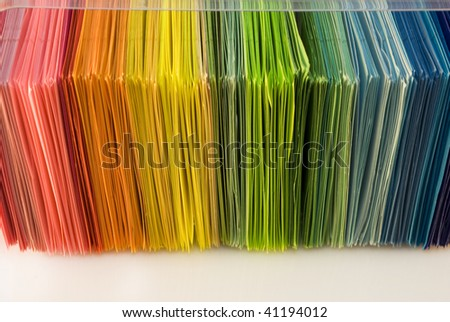 Various color sheets of paper scattered on white background - stock photo