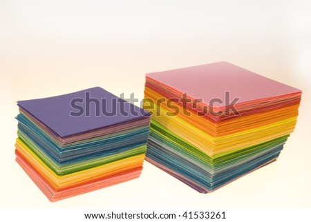 Various color sheets of paper scattered on white background