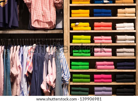 Various color shirts at shelf in shop - stock photo