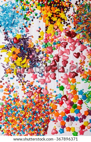 Various color sprinkles scattered on white wooden table - stock photo