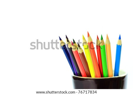 Various colored pencils in black cup on white background. - stock photo