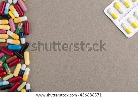 Various colorful capsules and pills on brown craft paper - stock photo