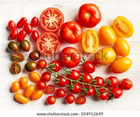 various colorful tomatoes on white wooden table, top view