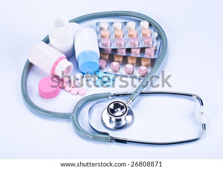 Various colour pills and stethoscope on a white background