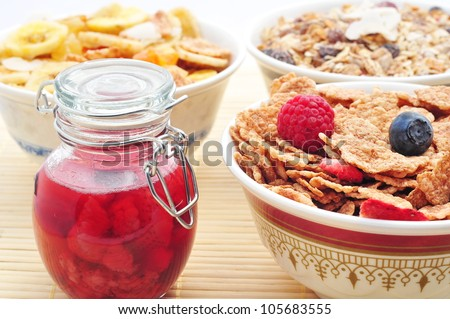 Various corn flakes with fresh fruits and jam - stock photo