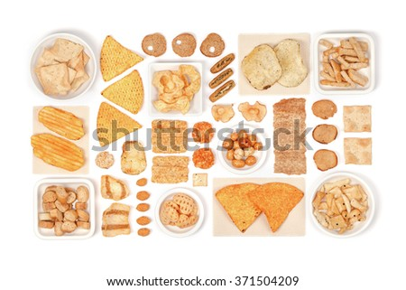 various crisps and snacks on white background above view - stock photo