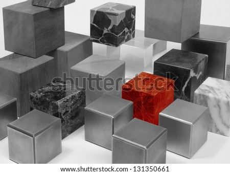 various cubes made of different materials, black and white toned including a outstanding red one - stock photo