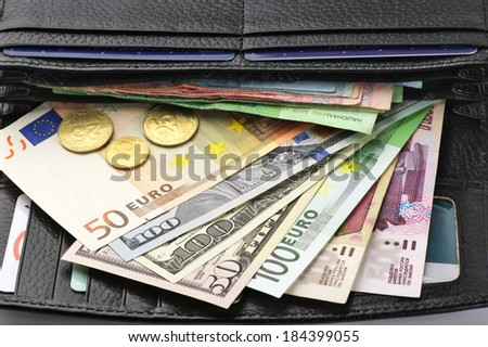 Various currencies in purse close-up. - stock photo