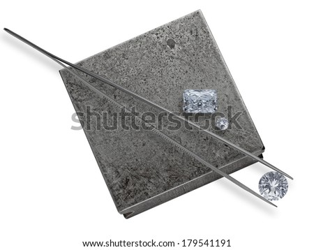 various cut cluster of diamonds and tweezers on a working jeweler anvil - stock photo