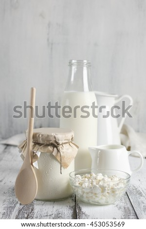 Various dairy products on rustic white wooden table: bowl of cottage cheese, jar of sour cream with wood spoon. bottle of milk and jugs. Selective focus on foreground.