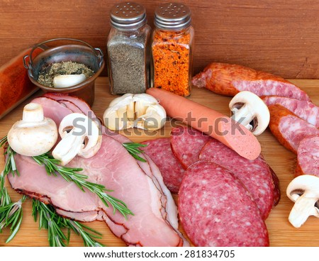 Various delicious low fat meats, salamis and sausages with raw fresh mushrooms and herbs. Mediterranean cuisine.Close up. Selective focus - stock photo