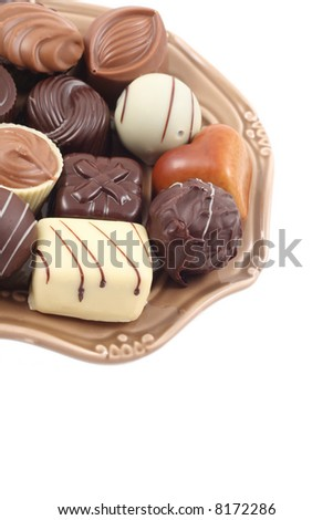 various delicious pralines on plate isolated on white