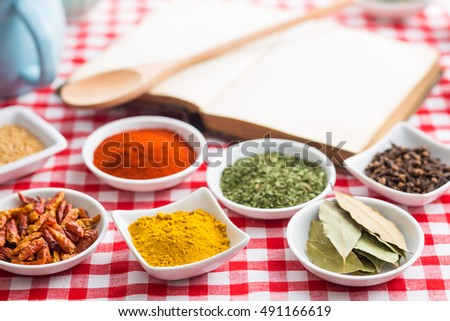 Various dried herbs and spices on checkered tablecloth.