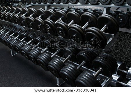 Various dumbbells in gym - stock photo