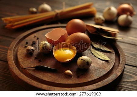 Various eggs and spices on a rustic aged wooden carving board at wooden tabletop - stock photo