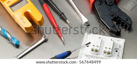 Various electrician tools and components including a multimeter, screwdrivers, wirecutters, drill bits, switches and sockets. Web banner format.