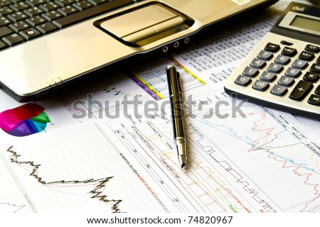 Various financial charts on the table with laptop, calculator, and pen - stock photo