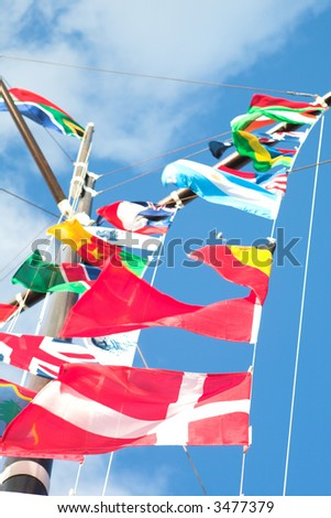 Various flags of various countries displayed together on a signal mast of a ship (focus on the red flags at the bottom)