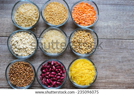 various food ingredients : beans, legumes, peas, lentils in wooden spoon and glass bowls - stock photo